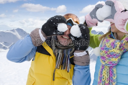 man and woman holding snowballs in