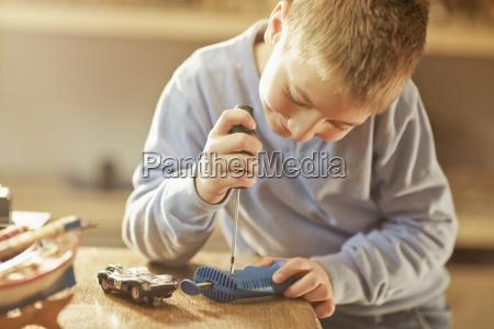 junger junge der mit spielwaren basteln