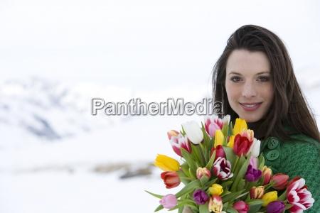 portrait einer jungen frau haelt bouquet
