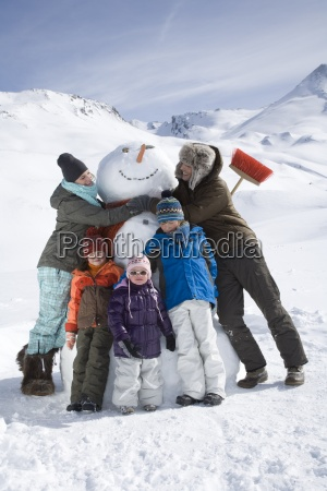 portrait of young family with snowman