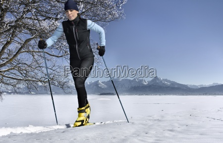 mid adult woman cross country skiing