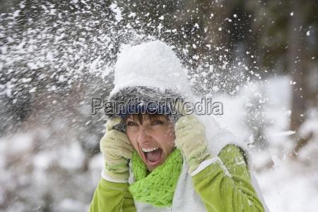 schreiende frau sich mit schneeball getroffen
