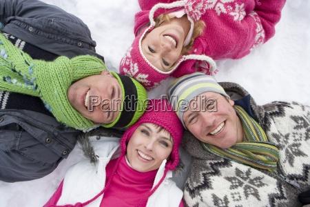 laechelnde familie im schnee im kreis