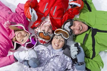 laechelnde familie die im schnee mit