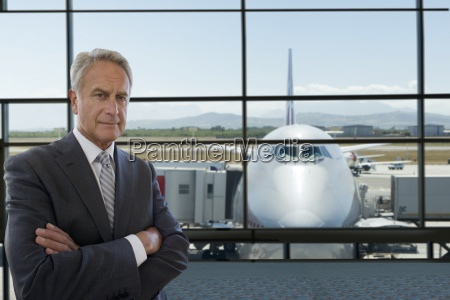 serious businessman standing in airport terminal