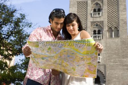junges paar blick auf touristische karte