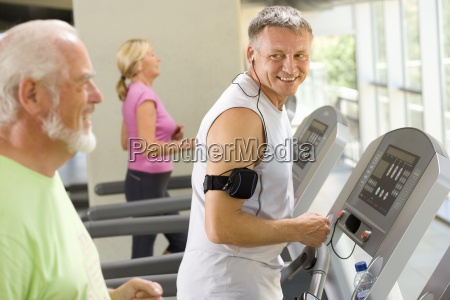 mature man on treadmill smiling at