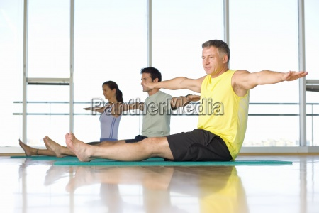 two men and woman taking exercise