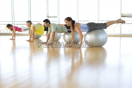 people taking exercise class balancing on