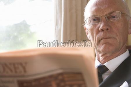 senior businessman in glasses reading newspaper