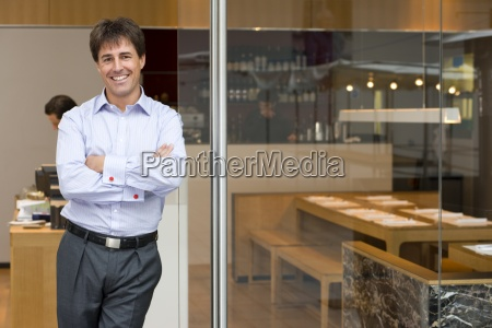 businessman in doorway of restaurant smiling