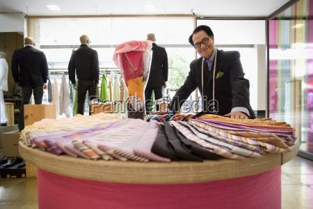 male shop assistant adjusting ties on