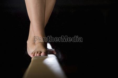 weiblicher gymnast auf schwebebalkenniedrige abschnitt