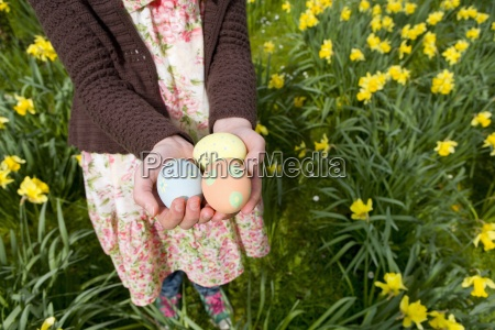 young girl holding decorated easter eggs