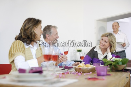 mature couples having dinner together at
