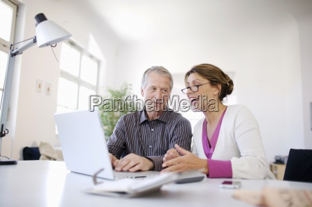 mature couple using laptop together at