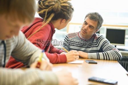 teenage student getting help from teacher