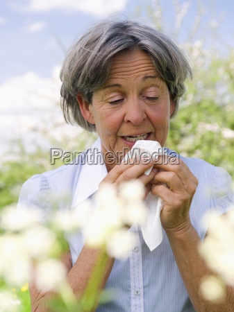 senior woman with allergies outdoors