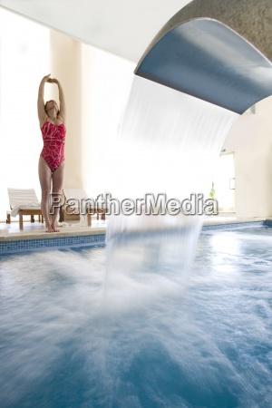 frau im badeanzug dehnung am rand