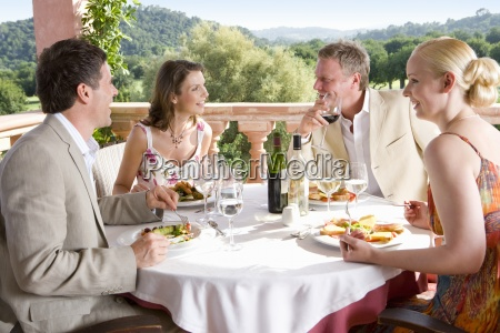 well dressed couples dining at table