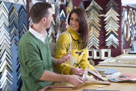 salesman helping customer in frame shop