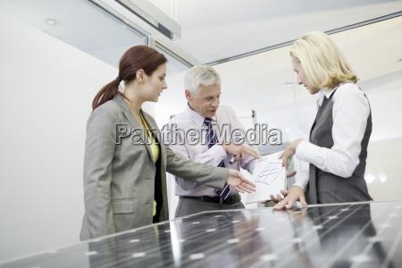 tres empresarios que discutem tecnologia de