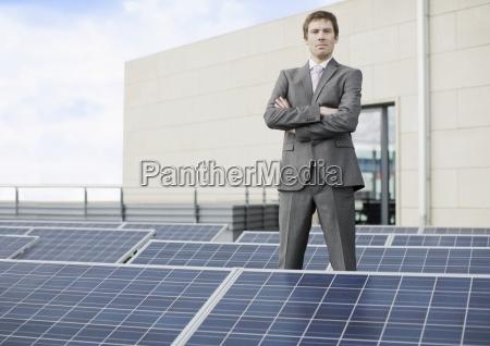 a businessman standing amongst solar panels