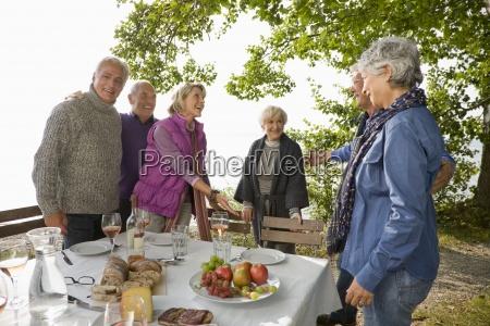 three senior couples having lunch outdoors