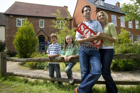 family of four with sold sign