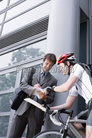 bicycle courier delivering package to businessman