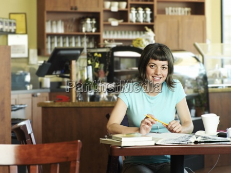 young woman studying at cafe table