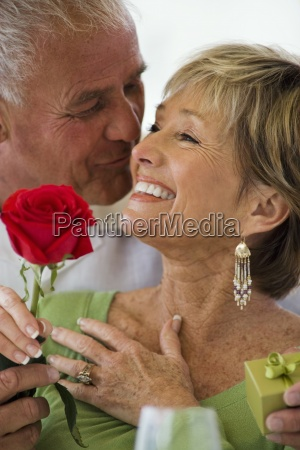 senior man surprising senior woman with