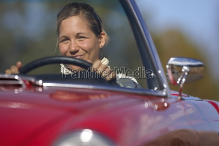woman driving red convertible car smiling