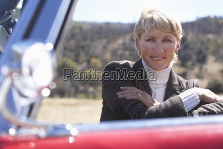 woman standing beside car door smiling