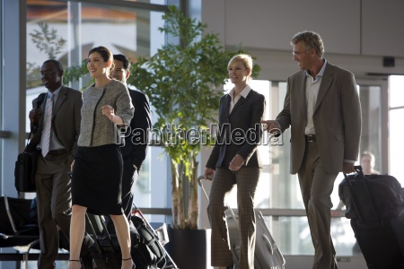 business colleagues walking with luggage smiling