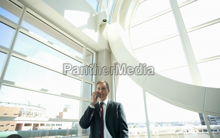 businessman using mobile phone beside large
