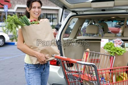 frau laden auto mit einkaufstueten vom