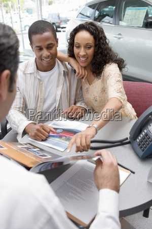 salesman and young couple sitting at