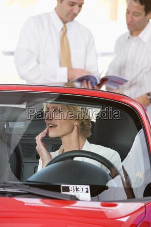 frau sitzt im roten cabrio im