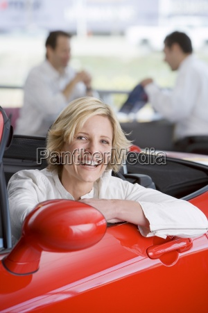 verkaeufer mit kunden im autoausstellungsraum eine