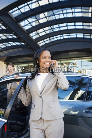 businesswoman alighting car outside hotel using