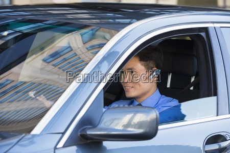 businessman driving in car using mobile