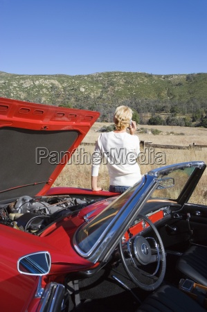 woman standing beside red convertible car