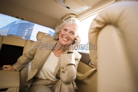senior businesswoman sitting in back seat