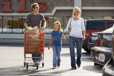 family leaving supermarket man pushing shopping