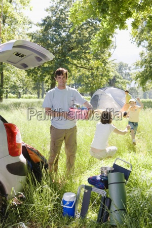 family unloading car on camping trip