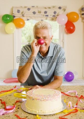 senior mann zu hause neben geburtstagskuchen