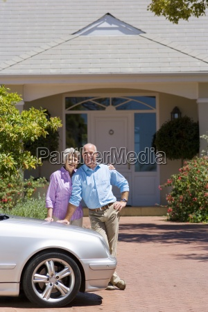 senior couple standing beside parked car
