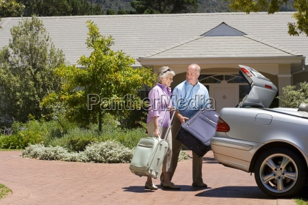senior couple loading suitcases into parked