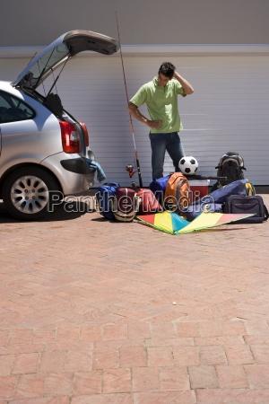 man lastning campingudstyr ind parkeret bil